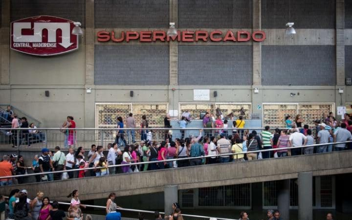 Lines at the supermarket go on for miles and hours - armed policemen stand by the food.