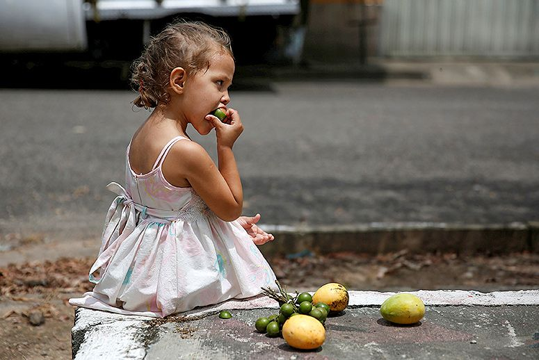 WARNING: UPCOMING GRAPHIC PHOTOGRAPHS. NOT FOR THE FAINT OF HEART.  Children are dying from starvation and malnourishment. This beautiful little girl enjoys fruit on the street and looks quite healthy compared to most of the children in Venezuela coverage.