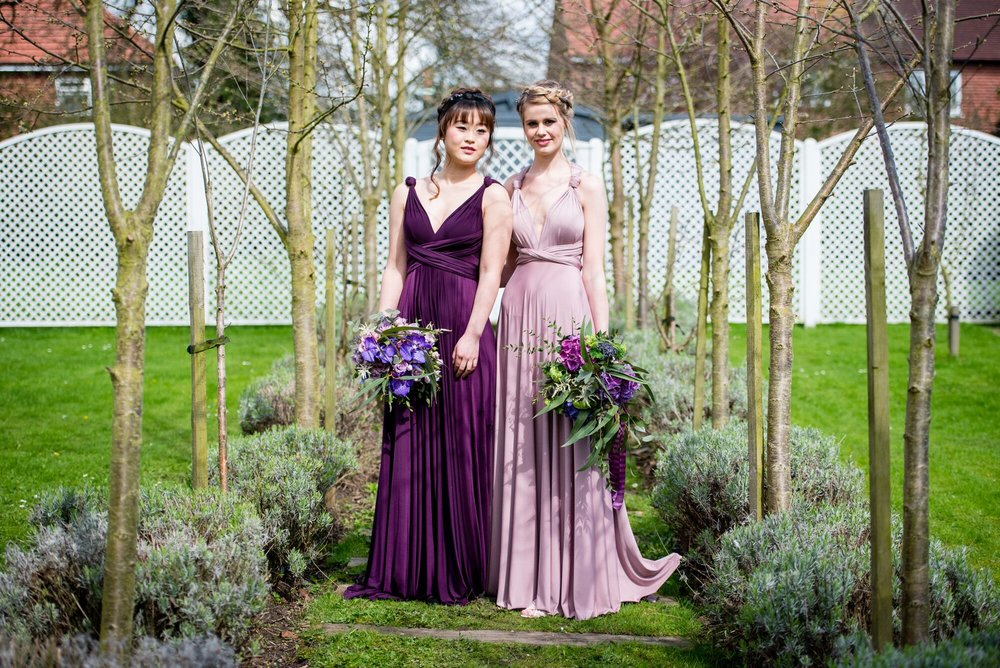 Models wear Two Birds Bridesmaids from Iconic Bride, Nottinghamshire. Colours Aubergine & Heather.. Did you know that in the USA it is the bridesmaids who pay for the brides dress?