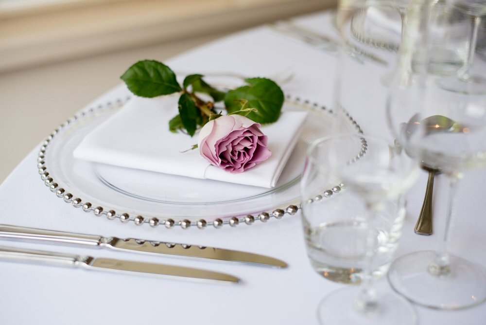Real flowers are a beautiful addition to any wedding table and give your guests enjoyments of beautiful fragrances. However if you are looking to keep costs down use of a silk flower may provide a cheaper alternative. Ask your local florist for top tips and ideas. Table setting by the Old Vicarage.