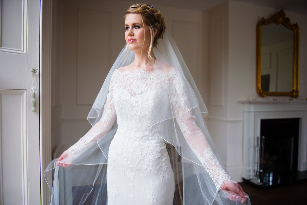 A long single length cathedral veil elegantly frames the silhouette and completes the bridal look. Image Credit: Geoff Kirby Photography.