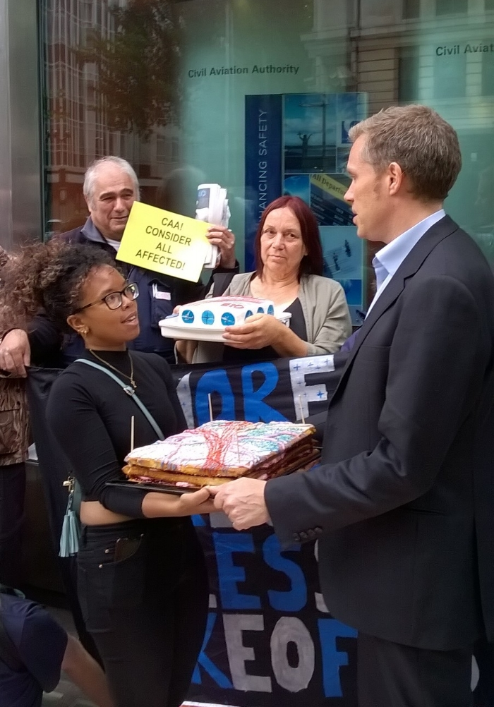 HACAN East community campaigner  Amina Gichinga presents cake to CAA's Tim Johnson