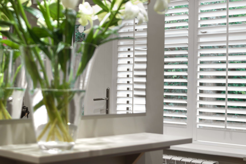 White plantation shutters controlling the amount of light that is filtering into a Salon.