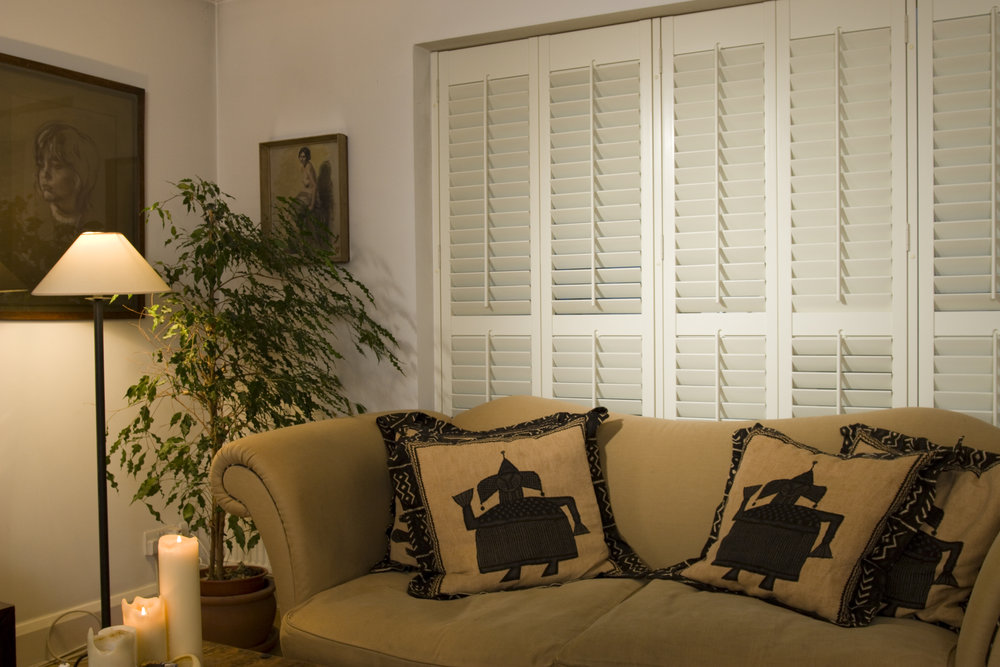 White plantation shutters tilted shut to allow privacy in a living room.