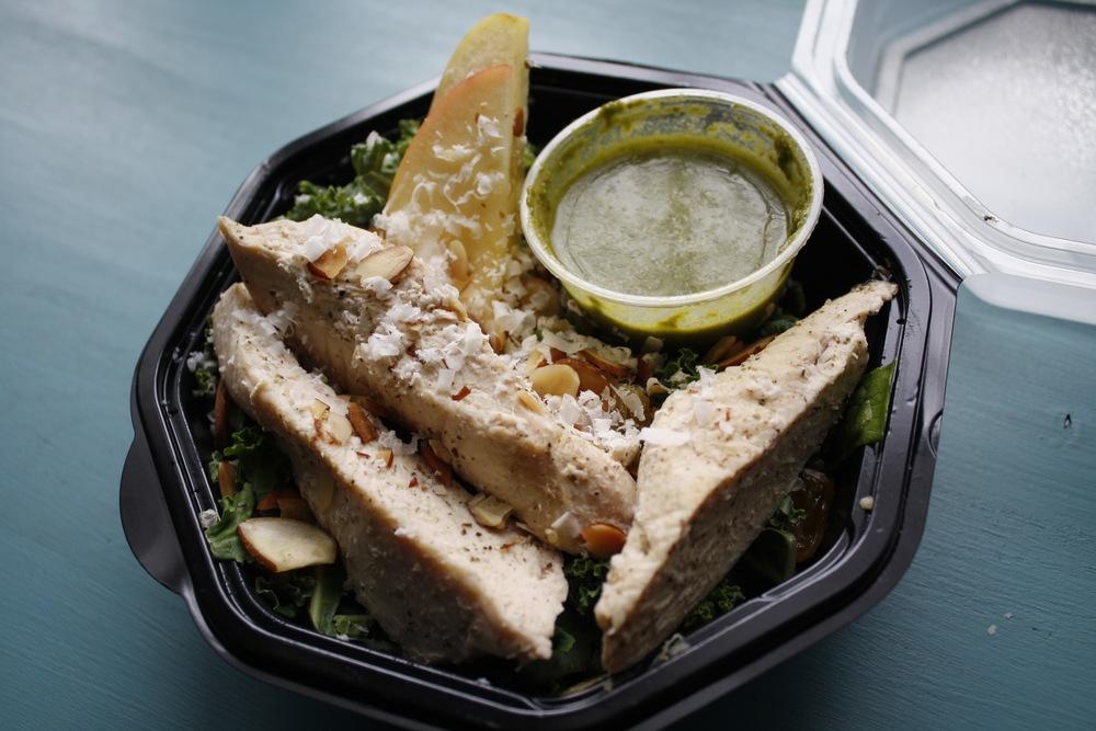 Salad with Kale, Toasted Almonds, Parmesan, Golden Raisins, Quinoa, Poached Chicken, Lemon Parmesan Vinaigrette.
