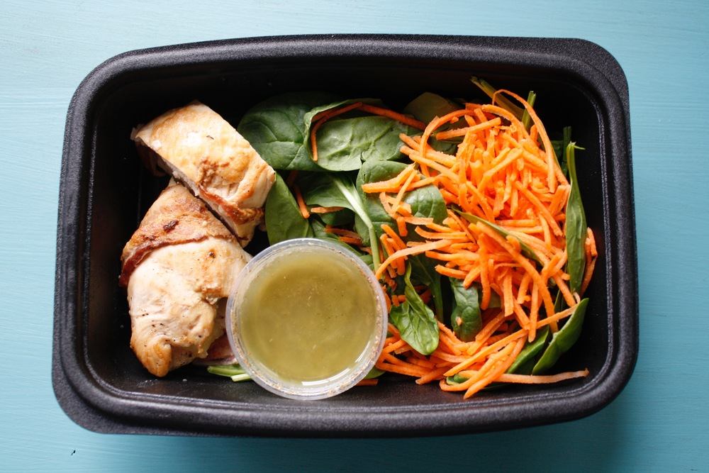 Organic spinach salad with carrots and bacon-wrapped chicken stuffed with fresh mozzarella