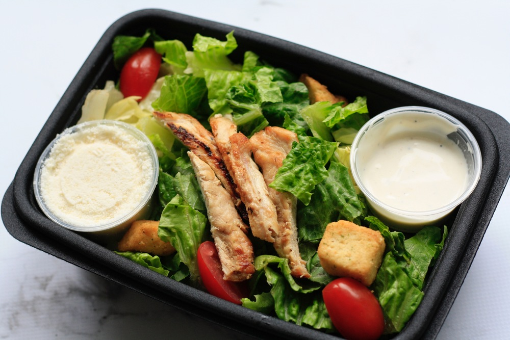 Chicken Caesar Salad Ingredients: Local chicken breast, organic grape tomatoes, croutons, lettuce, organic Caesar dressing