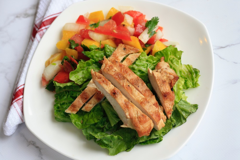 Baby Greens Salad with Mango Pico de Gallo Ingredients: Organic spinach and romaine, local chicken breast, organic mango, organic tomato, onion, organic cilantro, salt