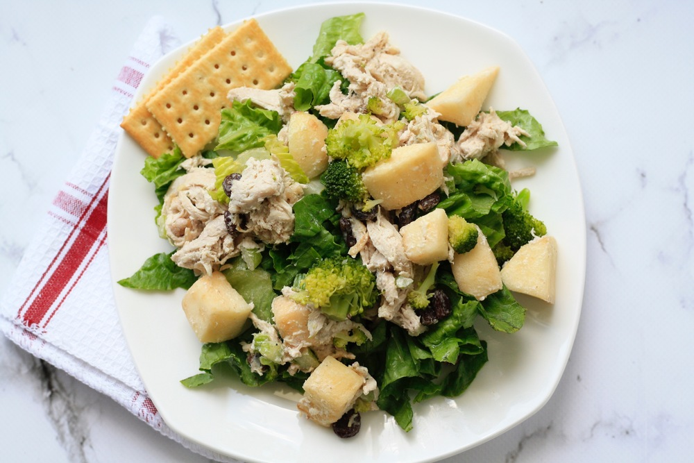 Chicken salad over a bed of baby mixed greens with crackers Ingredients: Local organic chicken breast, organic romaine, raisins, apples, crackers, broccoli