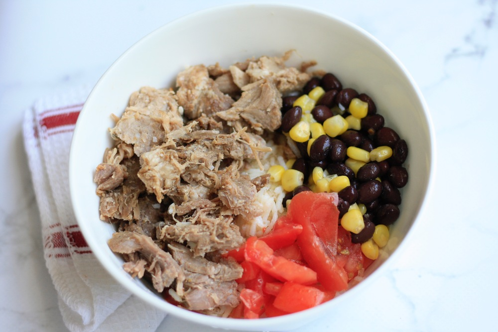 Pork taco bowl with black bean salad and fresh veggies Ingredients: Pork, organic basmati rice, black beans, corn, tomato, sour cream, salsa  One serving: 33g protein, 67g carbs, 21g fat,596cal