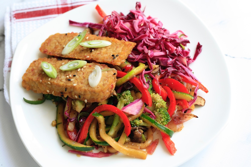 Veggie Stir Fry with Tempeh Ingredients: organic red onions, organic zucchini, organic Crimini mushrooms, organic red peppers, organic broccoli, organic garlic, organic ginger, red cabbage sesame salad, cranberry dressed tempeh, scallions, sesame seeds. One serving: 22g protein, 46g carb, 29g fat (504cal)