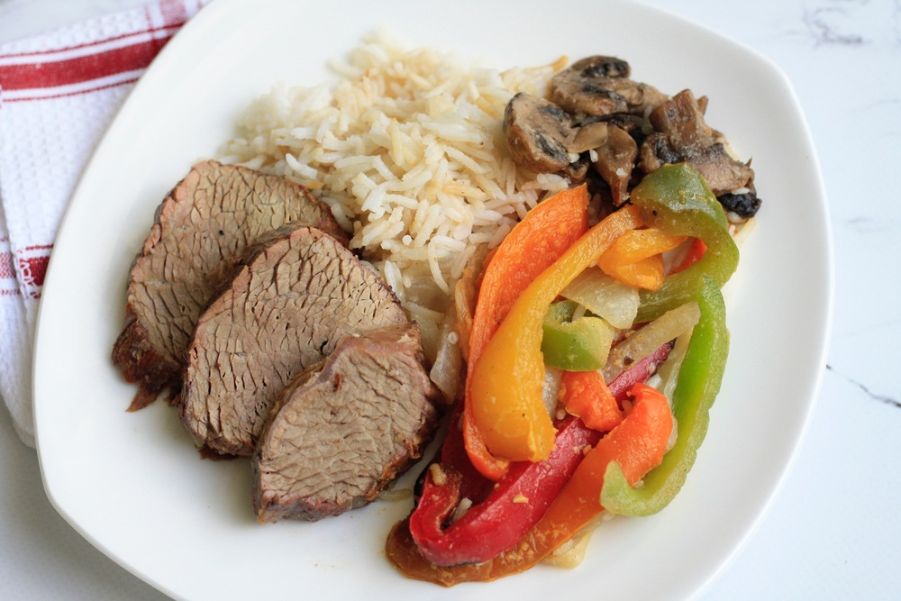 Daniel's Strip Steak over Basmati Rice with Sauteed Onions, Peppers, and Mushrooms Ingredients: All-natural beef, organic basmati rice, mushroom, organic bell peppers, and onion.  One serving (standard): 31g protein, 56g carbs, 19g fat (516 cal)