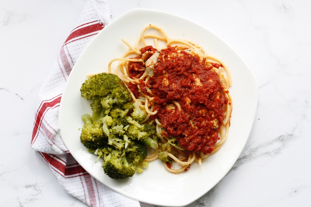 Chicken Parmesan over Spaghetti Ingredients: Local organic chicken, organic broccoli, egg, flour, parmesan, oregano, basil, garlic, thyme, marinara sauce, spaghetti, salt, pepper    One serving: 36g protein, 56g carbs, 14g fat (541cal)