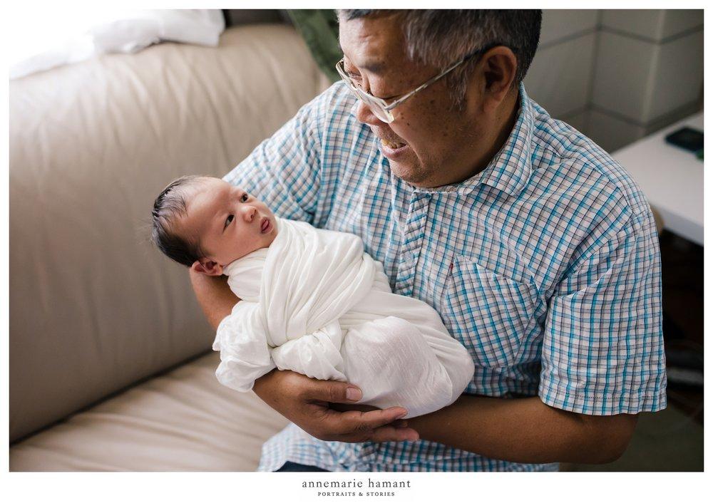 grandpa holding newborn baby