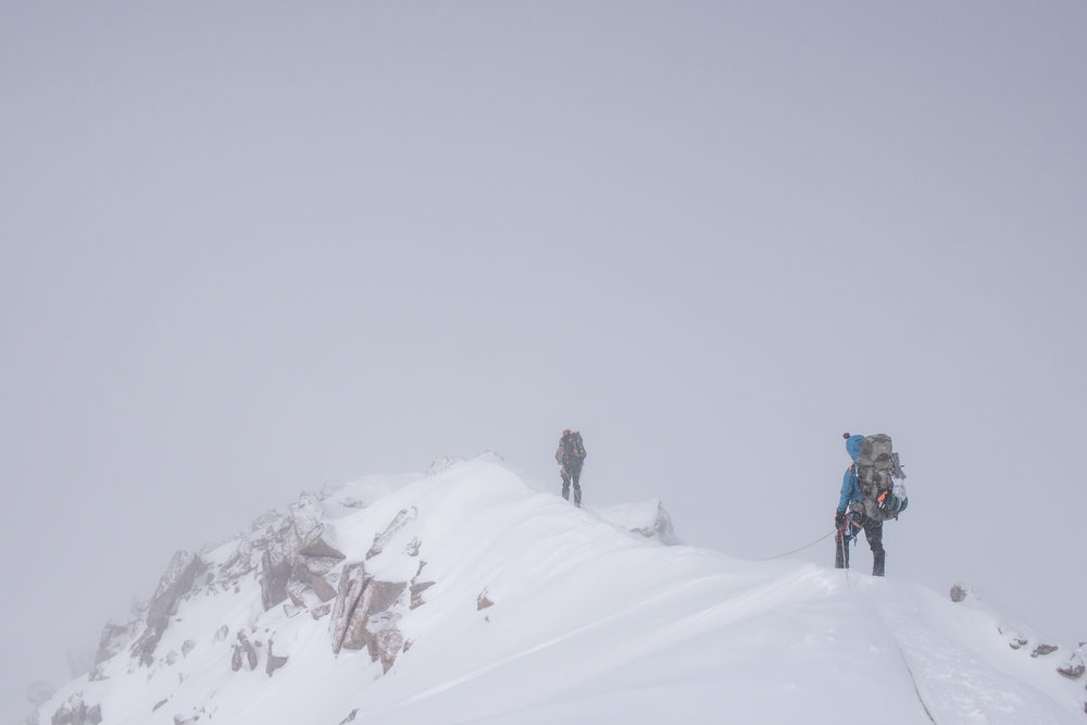 Climbing across the ridge in whiteout conditions.
