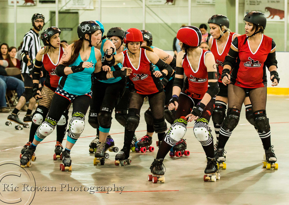 Blockers from the Bavarian Barbarians (Blue) try to hold back the Lady Macs Jammer (Red, center)