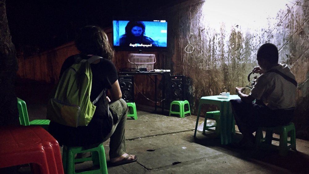 "Watching ""10,000 BC"" at a streetside cafe in Yangon, Myanmar; my partner Sarah on the left."