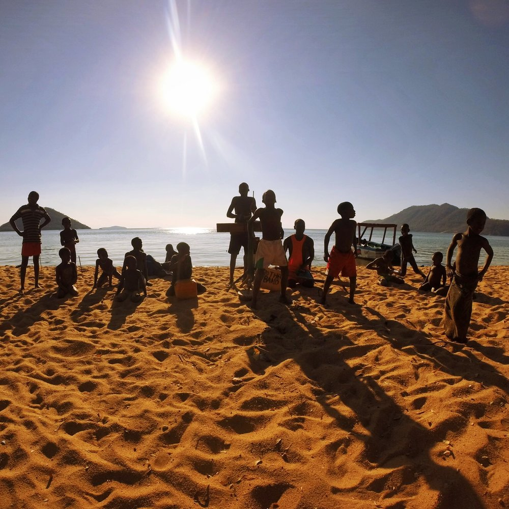 "A dozen boys on the shore of Lake Malawi, entertaining tourists with a localized rendition of ""Who Let The Dogs Out."""