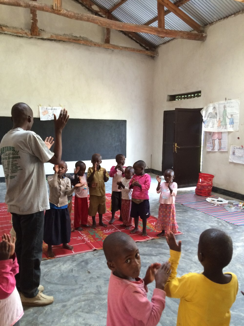 Headteacher Gabriel helps the children with their singing games.