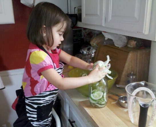 My oldest daughter a few years back helping to shove cucumbers, garlic scapes and onions into waiting a waiting mason jar.