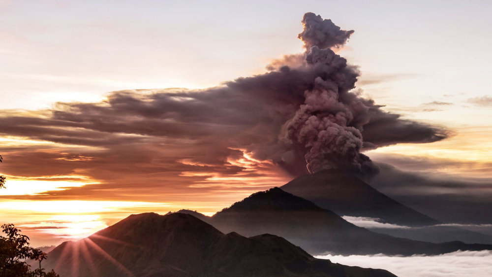 Ash and smoke pouring out of Mount Agung and high up into the atmosphere over the tropical island of Bali, Indonesia..