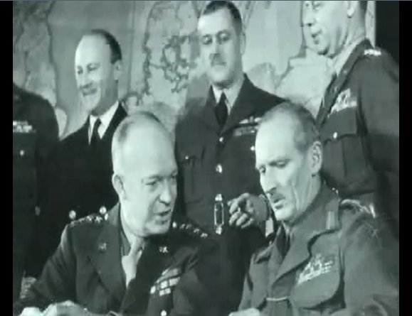 """Captain James Martin Stagg (front right) in discussions with General Dwight """"Ike"""" Eisenhower (front left)"""