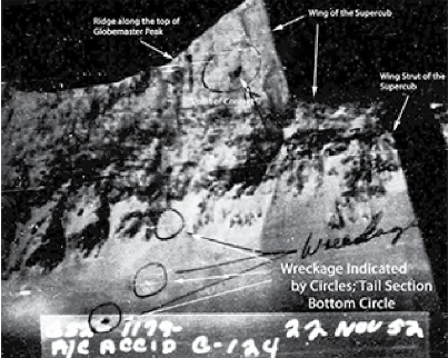 """This reproduced image was appended to the official """"Report of an Air Force Major Aircraft Accident Involving C-124A No. 51-107A"""". The upper circle is annotated """"Point of Contact"""", the three lower circles are annotated """"Wreckage"""". The impact point was assumed based on the point where an avalanche seemed to have emanated. The date on the photograph reflects the date of the accident - not the date the picture was taken. The photograph was taken at an altitude of about 9,500 feet looking from a point approximately three to five miles east of the crash site. Courtesy US Air Force; book entitled  """"Letters from the Globemaster Families: The Lost C-124 of Mount Gannett, Alaska"""" )"""