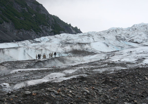 A group of visiting military members stand on Colony Glacier above the aircraft debris field actively being excavated during June 2017; (Photo courtesy Laurel Andrews/Alaska Dispatch News)