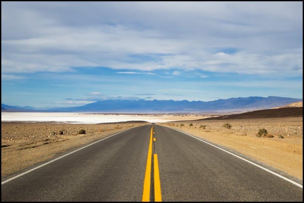 Asphalt roadway near the salt flats of Death Valley National Park in California
