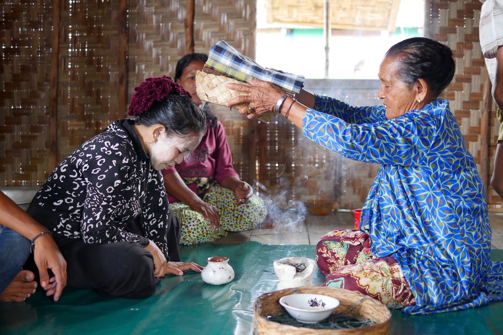 Respected Bajau elder, Mbo Sayatina, right, performs a ritual to ensure a safe pregnancy for a soon-to-be mother.