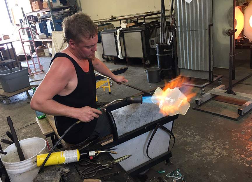 Alex Abajian of Glow Glass Studio heats the Lazarus vase just before applying the eyes and decorative wrap.