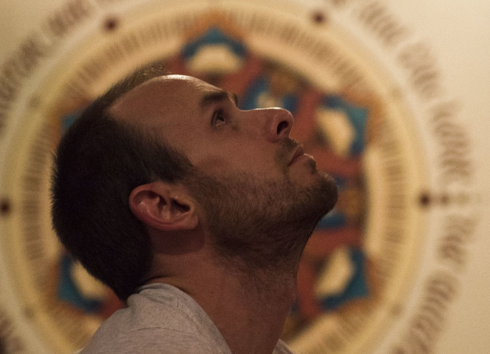 "Mat Chandler, 30, locks his gaze on the ceiling while practicing yoga in Aurora Healing Arts center. The mural behind him is based around Chandler's guiding life mantra – ""Be Here Now."""