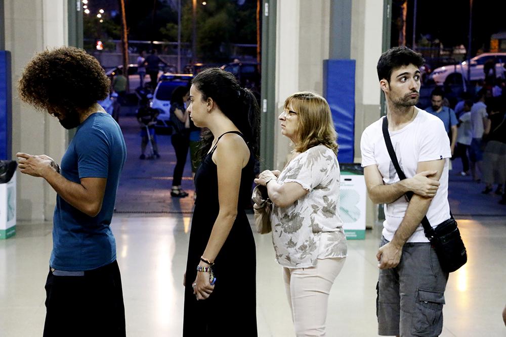 Participantes del mitin hacen fila en el ingreso del pabellón de la Estació Nord de Barcelona donde Podemos organizó un evento de ingreso libre para la espera de resultados.