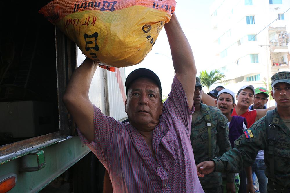 Don Carlos ayuda a descargar y repartir donaciones provenientes del cantón Samborondón | Foto: M. Ayala