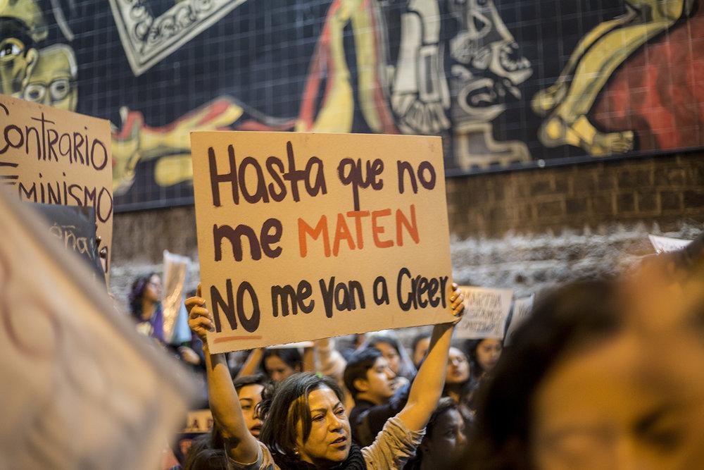 Una mujer sostiene un cartel frente al mural que adorna la fachada sur de la Fiscalía General del Estado en Quito. Tras el ataque, Martha fue hallada inconsciente y desnuda en el baño del local. Según su abogado, ella tenía sangre en sus partes íntimas y a su alrededor había objetos con rastros de sangre, botellas de licor, vasos de cristal y ropa de los sospechosos, entre otros efectos. Según las investigaciones, los presuntos violadores uno por uno habrían abusado de Martha y además habrían introducido esos objetos en sus partes íntimas.