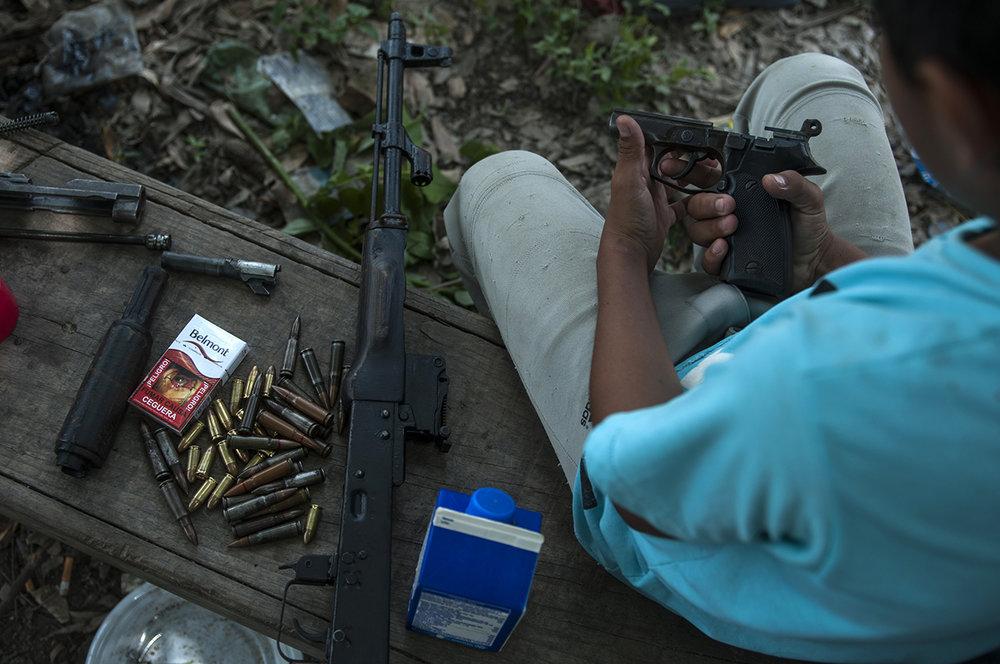 Un niño de la comunidad curiosea con las pistolas desmontadas mientras mientras el líder del Barrio 18 y sus amigos pandilleros lijan y pintan sus armas.