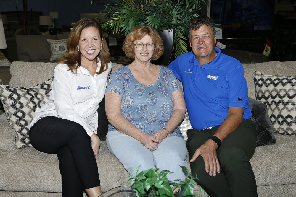 IMAGE DISTRIBUTED FOR AARON'S INC - (L - R) Andrea Freeman, Vice President of Marketing at Aaron's, Beth Chancey, winner of the Michael Waltrip Family Vacation Sweepstakes, and Michael Waltrip, racing legend, seen at an Aaron's store on Saturday, Nov. 19, 2016, in Miami. Beth Chancey, her husband and two friends enjoyed a shopping spree at Aaron's as part of her winning weekend getaway in Miami. (Joel Auerbach/AP Images for Aaron's, Inc.)