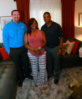 (L to R): Aaron's Regional Manager Daniel Stevens, new homeowner Keyona Thompson and former NFL star Warrick Dunn tour Thompson's new home filled with furniture, electronics and appliances donated by Aaron's as part of Homes for the Holidays (HFTH) program sponsored by Warrick Dunn Charities and Habitat for Humanity of Pinellas County.