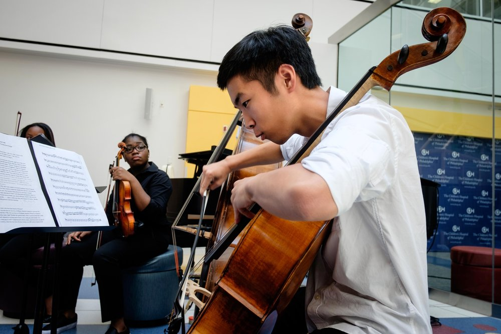 Nathan Kim demonstrates the distinct sound of the cello during an interactive performance at Children's Hospital of Philadelphia.