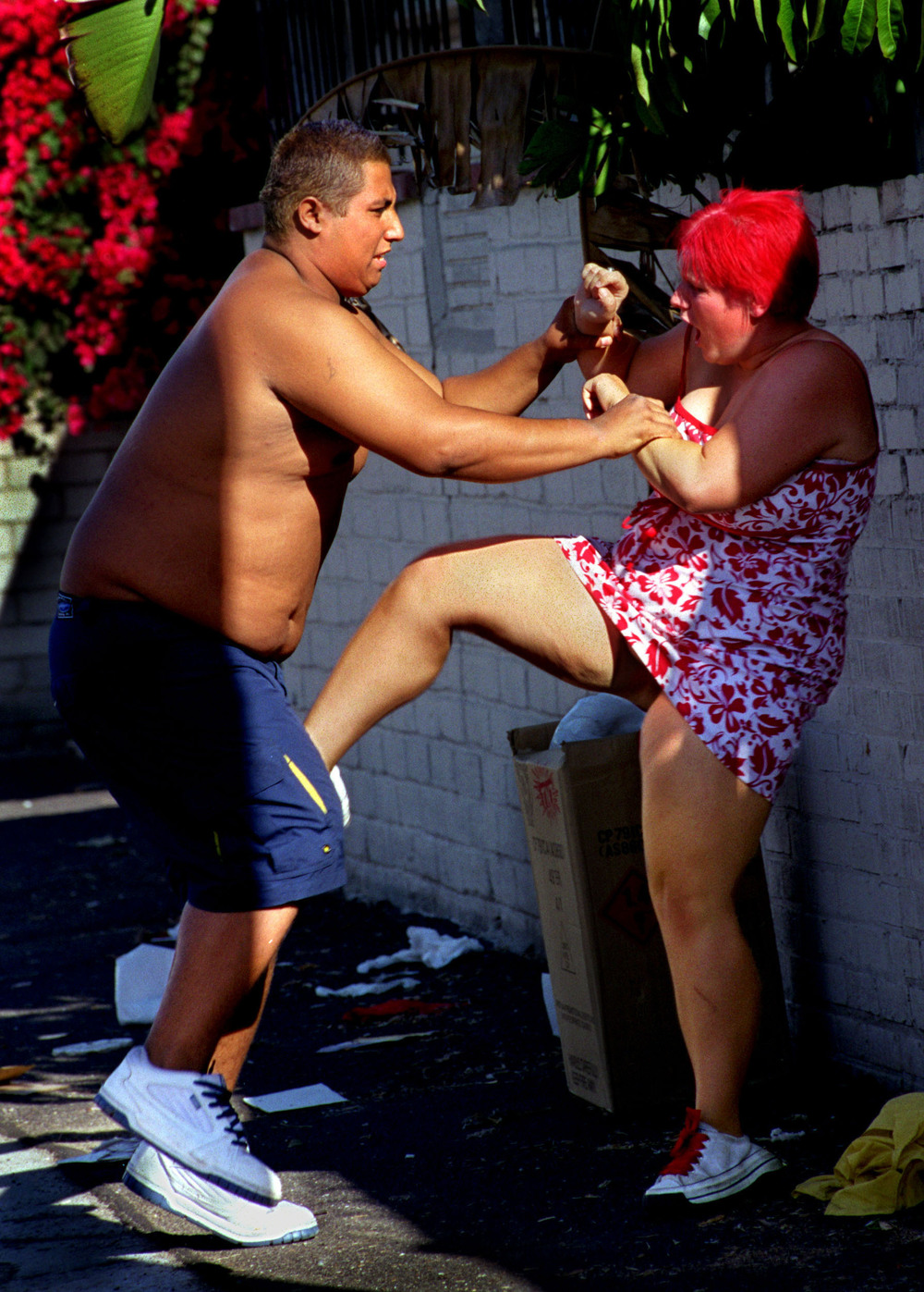 On a hot summer day, homeless and hanging out in the streets, newlyweds Sam and Janea get into a heated argument which quickly turns physical. He runs up to her in the alley, grabs her wrists, and the struggle begins. After he backhands her in the face, she kicks him in the groin. ©Gail Fisher Los Angeles Times