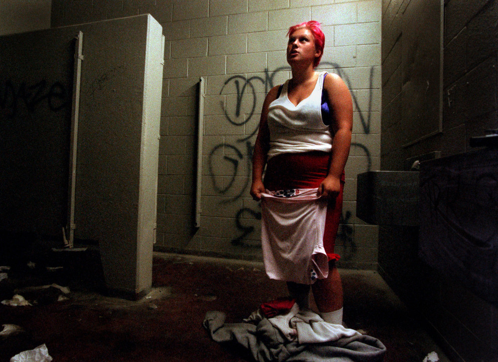 Unemployed and homeless, her husband in jail, life isn't what she thought it would be eight weeks after aging out of Orange County's foster system. Janea uses the squalid restroom at Belvedere Park to dress and wash. ©Gail Fisher Los Angeles Times