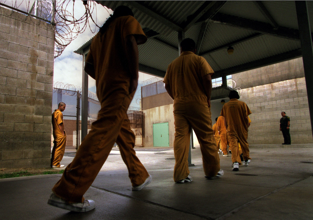 "Walking single file, inmates at Theo Lacy Men's Jail enter the mess hall to eat lunch.  ""I'm lost and lonely in here man. This is hell,"" Jesse says, on the verge of tears standing alone against the wall. ©Gail Fisher Los Angeles Times"