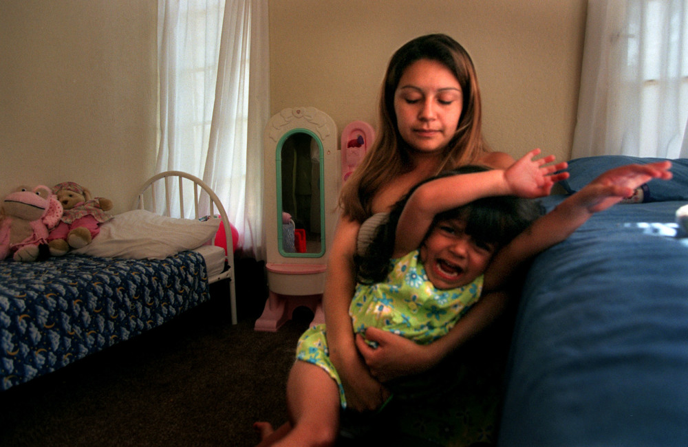 "A single teen, working mother, Monique at times struggles with her three-year-old. ""I can't force her to go to sleep. I can't hold her down and make her do it,"" Monique says. ©Gail Fisher Los Angeles Times"