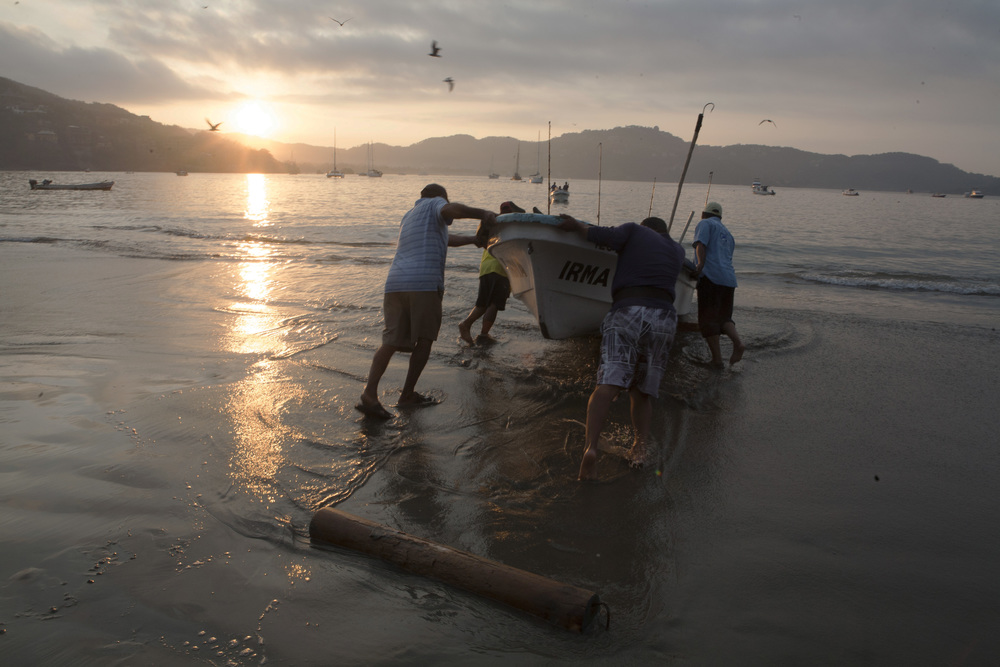 At the first rays of dawn, the morning light illuminates fishermen hauling up their boats on the main beach in Zihua. ©Gail Fisher