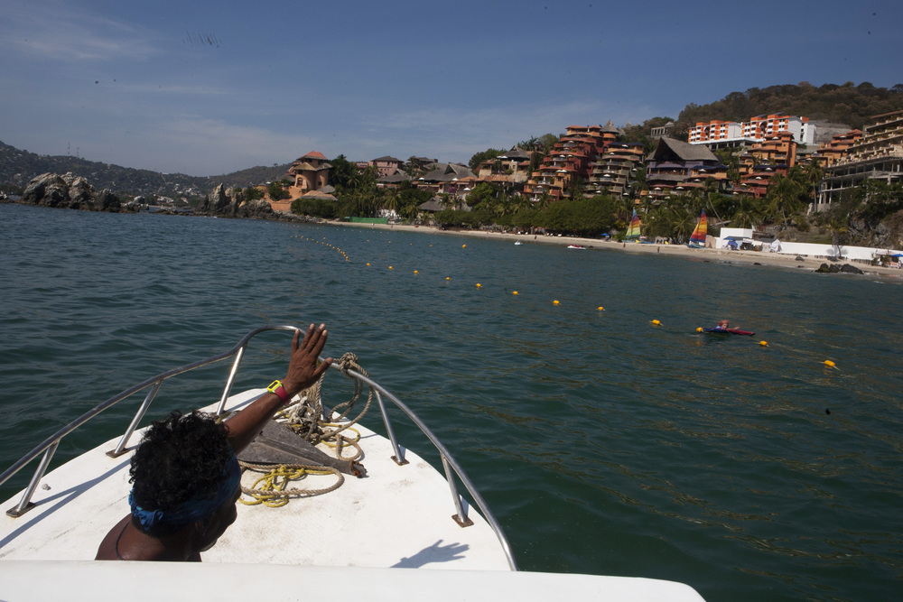 "From the perceptive of the ""Reny,"" our fishing boat, Polo Flores, guide, waves to a swimmer as he approaches Club Intrawest Vacation Club on the shore of Playa La Ropa where we were staying for the week in Zihua. ©Gail Fisher"