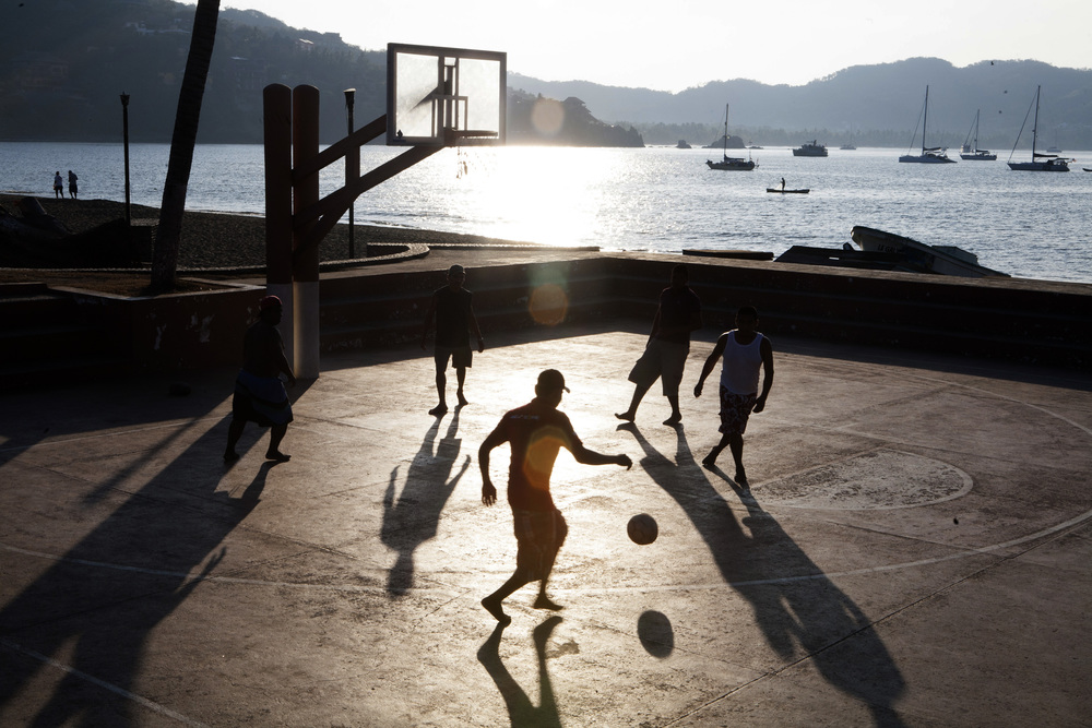 Locals enjoy a game of soccer in the early morning hours at the public basketball court on the waterfront in the main plaza in Zihuatanejo. ©Gail Fisher