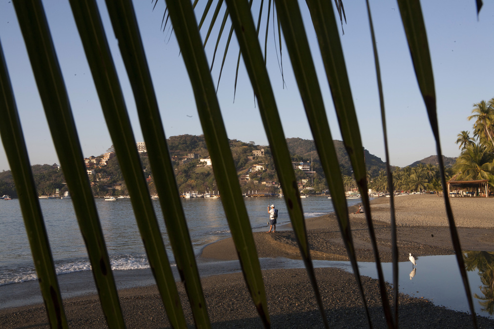Zihuatanejo, in the state of Guerrero, only four miles south of Ixtapa's bustling high-rise hotels, has a laid back vibe surrounded by cliffs, sand and sea. A fisherman tries his luck casting a line on Playa Principal. ©Gail Fisher