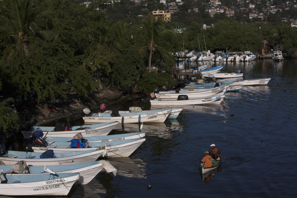 Fishing boats line the inlet leading to the Muelle Pier where water taxis ferry tourists to Playa Las Gatos, a popular beach for snorkeling, located across Zihuatanejo's Bay for 40 peso or $3 USD. ©Gail Fisher