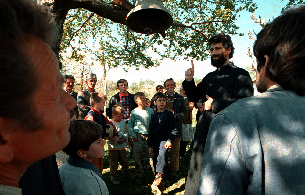 Villagers of Jeronisht gather around Father Martin Ritsi, an orthodox priest from Orange County who move to the Balkan Nation three years ago to help make a difference in their lives. ©Gail Fisher Los Angeles Times