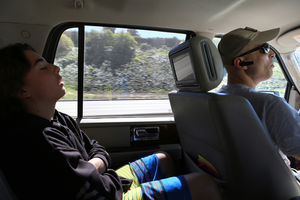 Gracie's son Kheydon, 13, left, ditches school and naps in the back seat as his father navigates his way through heavy Los Angeles traffic on his way to The Yard to train for an upcoming fight.  (©Gail Fisher for ESPN)